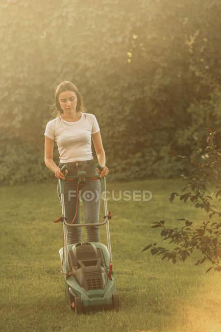Frau trimmt Gras mit Rasenmäher auf Hof — Stockfoto