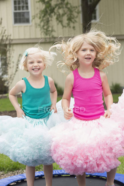 Portrait of happy siblings jumping on trampoline at backyard — Stock Photo