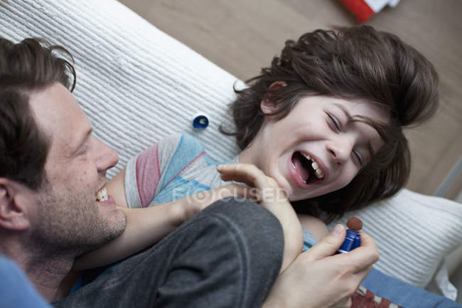 Close-up of Father and son fooling around on sofa — Stock Photo