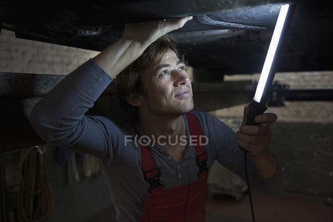 Mechanic holding illuminated fluorescent light while examining car — Stock Photo