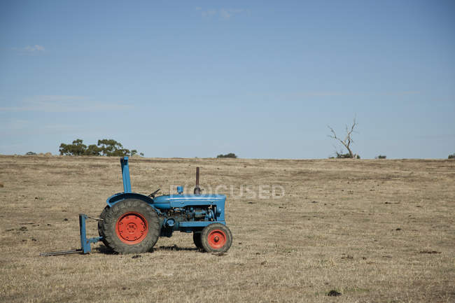 Tractor on empty field — Stock Photo
