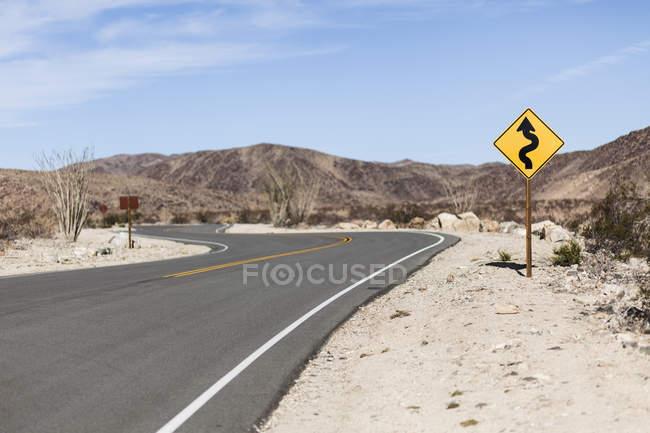 Направленная знак по дороге на обочине дороги на десерт местности — стоковое фото