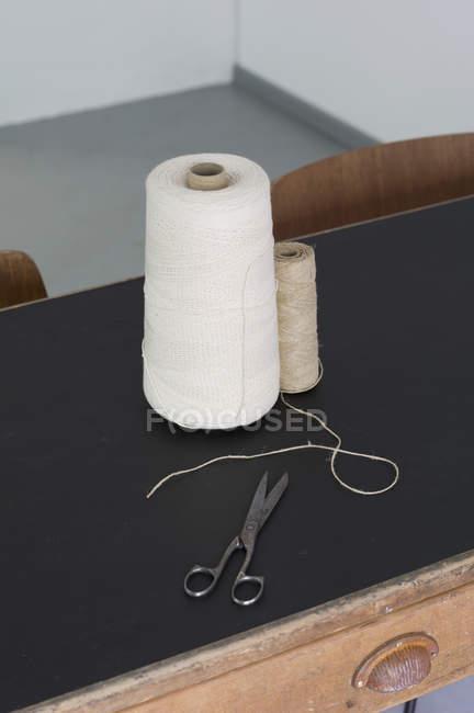 Vista da vicino di bobine di filo e forbici sul tavolo — Foto stock