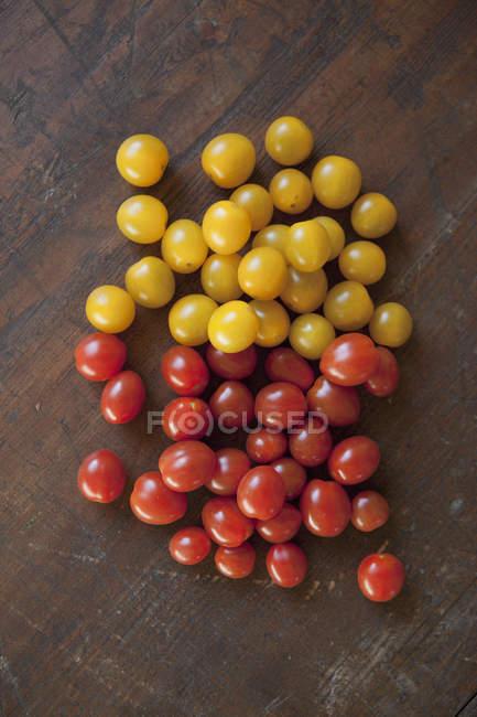 Directamente sobre la vista de tomates amarillos y rojos en la tabla - foto de stock