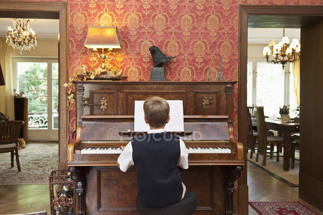 Rear view of boy practicing on old-fashioned upright piano — Stock Photo