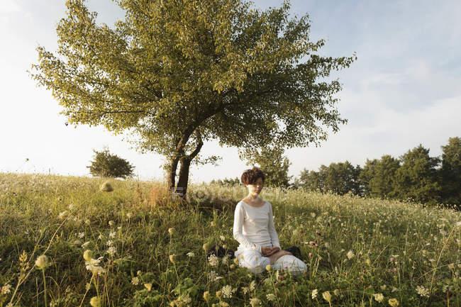 Жінка, розмірковуючи про трав'янистих області — стокове фото