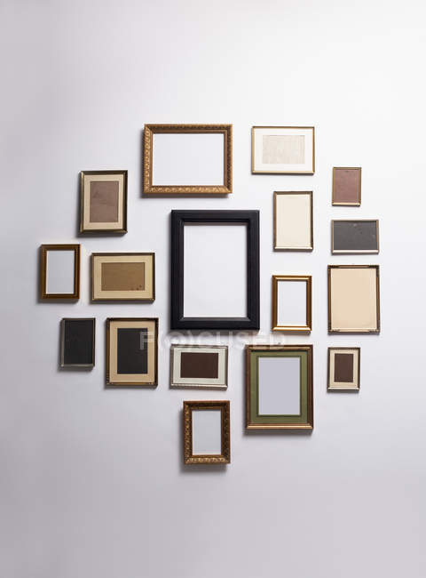 Various empty picture frames hanging on wall — Stock Photo