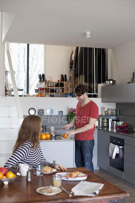 Mujer sentada en la mesa mientras el hombre prepara el desayuno en la cocina - foto de stock