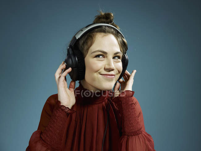 Portrait of young woman wearing headphones and smiling — Stock Photo