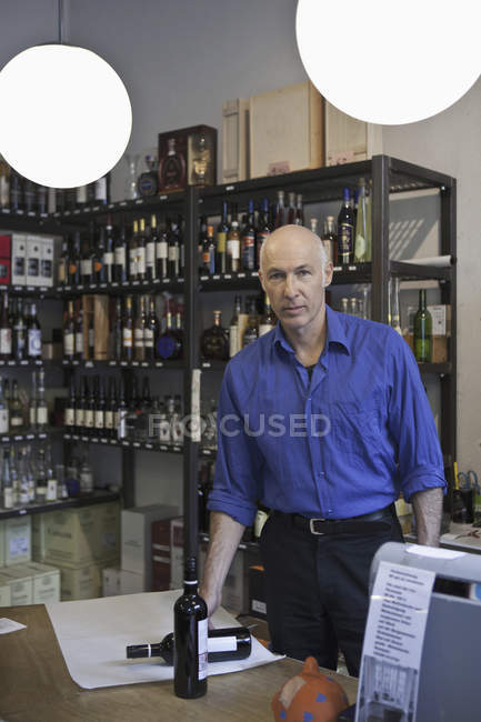 Portrait of Mature man standing in wine shop — Stock Photo