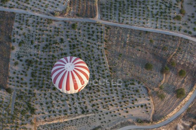 Vista de ángulo bajo de rayas globo aerostático volando sobre paisaje agrario - foto de stock