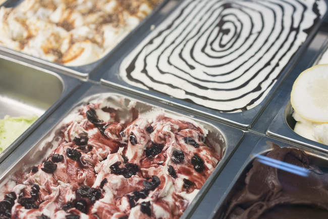 Close up view of colorful ice creams in containers on display at store — Stock Photo