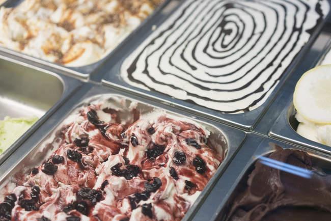 Крупным планом зрения красочные мороженое в контейнерах на дисплее в магазине — стоковое фото