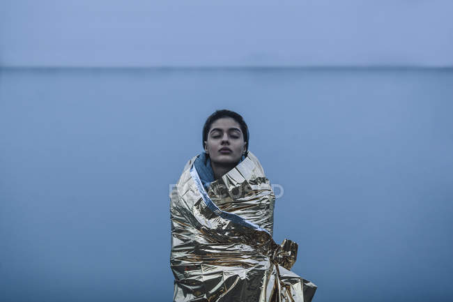 Девочка-подросток с закрытыми глазами, завернутая в золотой пластик, стоящий напротив озера — стоковое фото