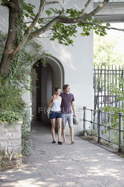 Young couple walking through pavement in front of building — Stock Photo