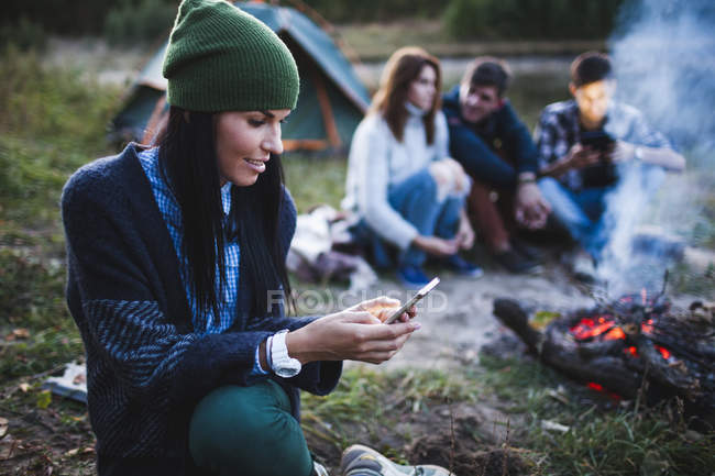 Young woman using mobile phone while friends sitting by bonfire at campsite — Stock Photo