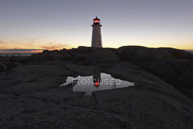 Surface level of paddle on rock reflecting lighten lighthouse on cliff over sunset sky — Stock Photo