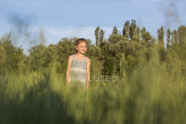 Uma jovem alegre de pé num campo olhando a vista — Fotografia de Stock