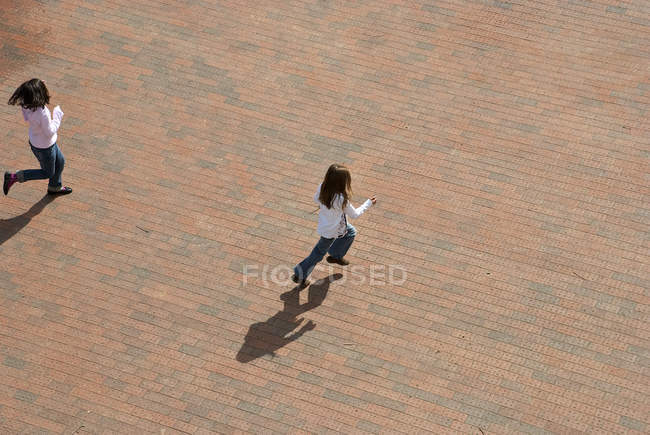 From above two girl skipping through urban plaza — Stock Photo