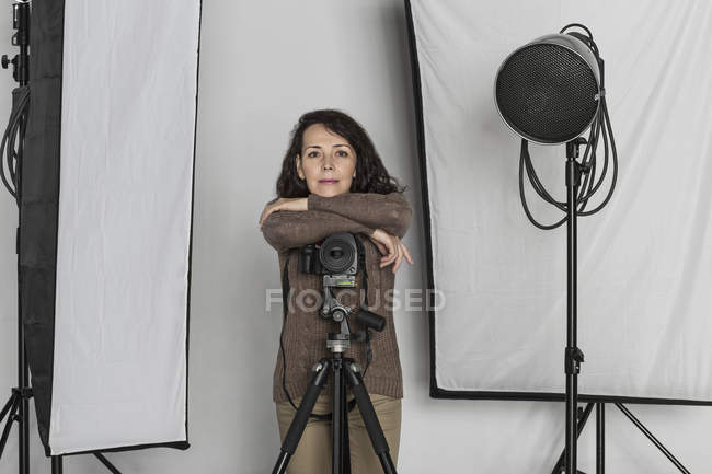 Portrait of confident mature female photographer leaning on camera tripod in photo studio — Stock Photo