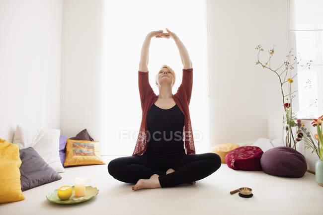 Forma de mujer sentada con los brazos alzados en el hogar - foto de stock