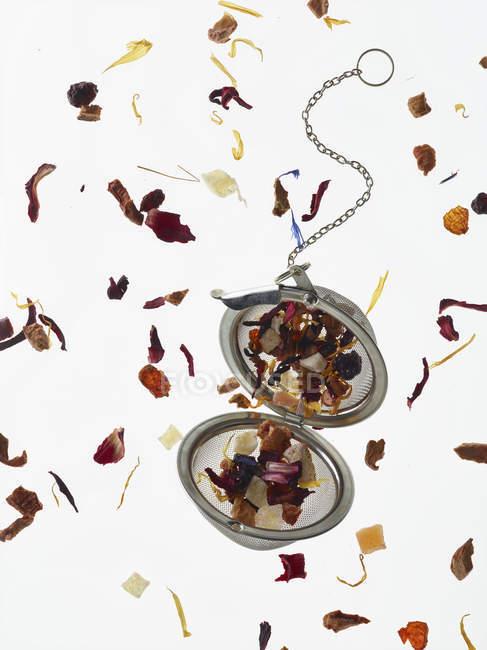 Vue du dessus des pétales à base de plantes et de la passoire à thé sur table blanche — Photo de stock