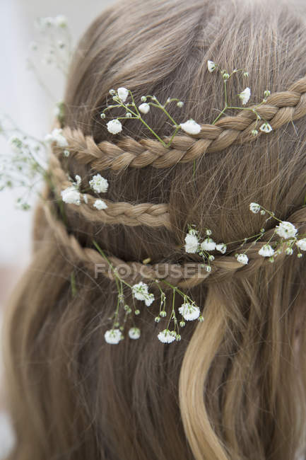 Close up view of flowers in braided hair — Stock Photo