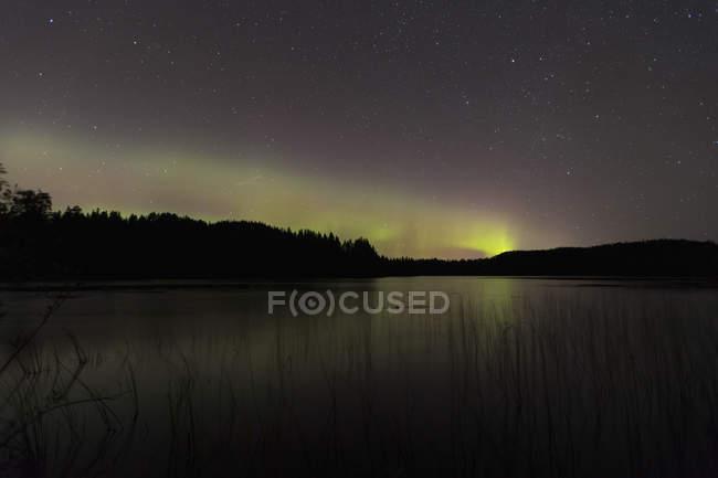 Idyllic view of aurora borealis at lake during night — Stock Photo