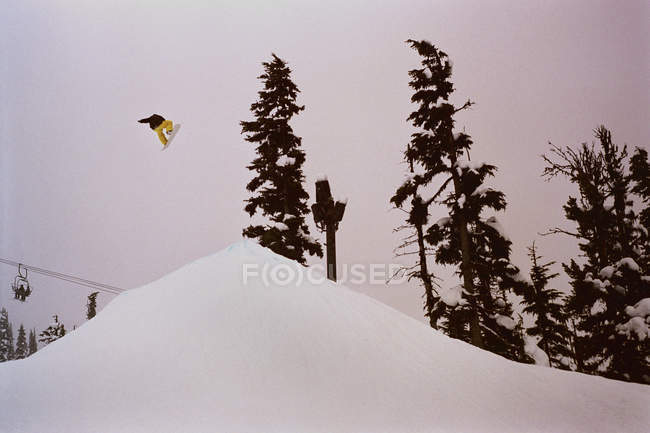Side view of snowboarder in mid-air over trampoline — Stock Photo