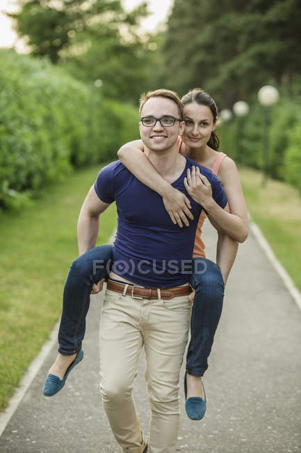 Man giving woman piggyback ride in park — Stock Photo