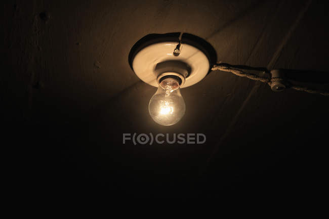 Low angle view of lit light bulb on ceiling — Stock Photo
