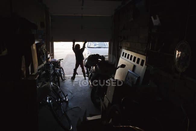 Ragazzo di Siluette indossando pattini e aprendo la porta del garage — Foto stock