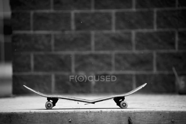 Vue latérale du skateboard cassé sur trottoir — Photo de stock