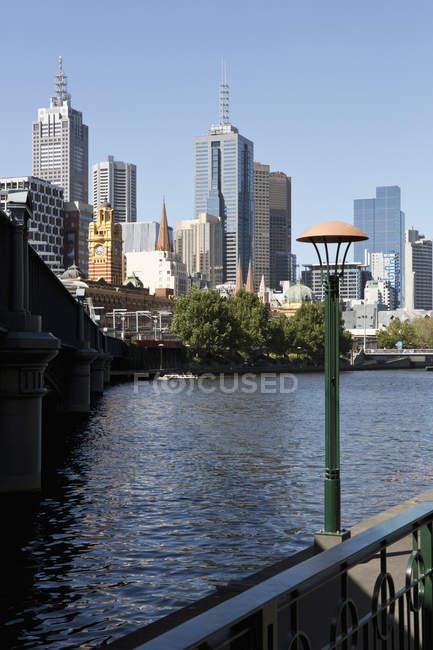 Vista distante de arranha-céus com mar em primeiro plano, Sydney, Austrália — Fotografia de Stock