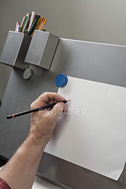 Обтинання чоловічого рукою спираючись на папері — стокове фото