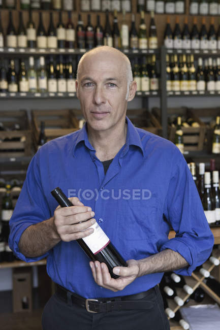 Portrait of Mature man holding wine bottle in wine shop — Stock Photo