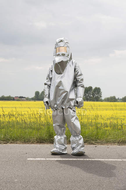 Person in a radiation protective suit posing against rape field — Stock Photo