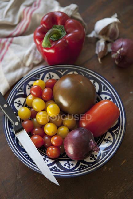 Висока кут зору помідори і ножем на тарілку — стокове фото