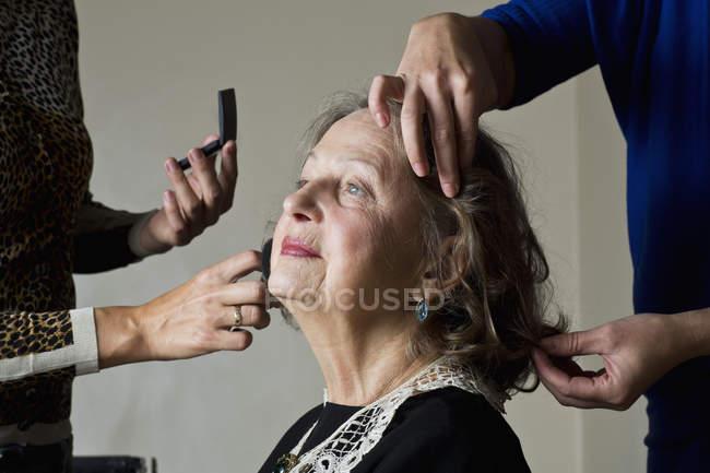 Maquiagem artista aplicando pó compacto no rosto da mulher — Fotografia de Stock
