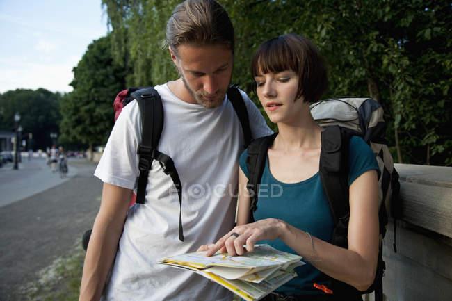 Молодий backpacker пара дивлячись на карті міста на відкритому повітрі — стокове фото