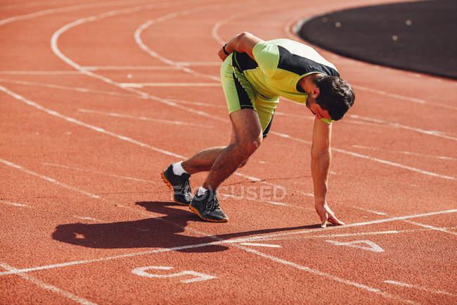 Полная длина молодого бегуна на стартовом блоке на трассе — стоковое фото