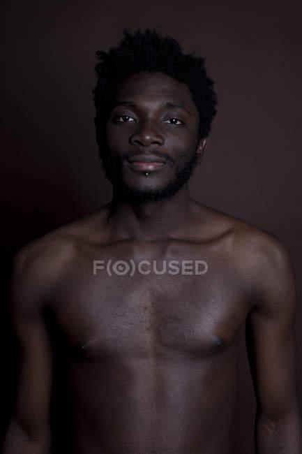 Un jeune homme à la hanche torse nu debout sur un fond brun, la taille haute — Photo de stock