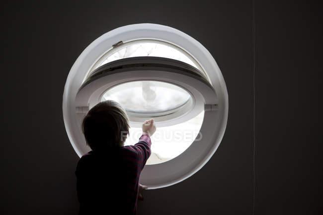 Rear view of boy reaching to open round window — Stock Photo