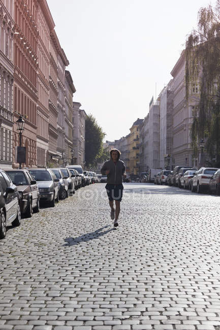 Mid adult man jogging through street in city — Stock Photo