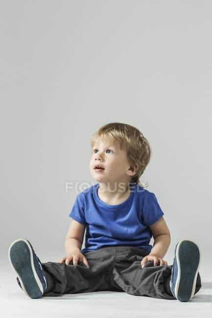 Повна довжина хлопчика в фанатів фотографіях хтось дивитися вбік над сірий фон — стокове фото