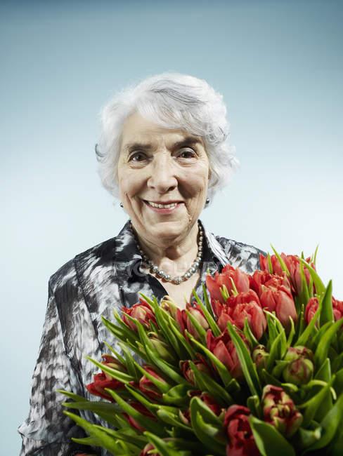 Seniorin hält Strauß Tulpen — Stockfoto