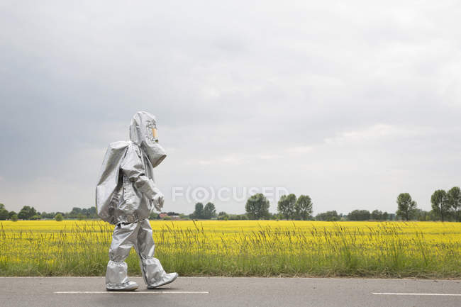 Person in radiation protective suit walking alongside oilseed rape field — Stock Photo