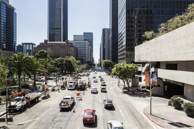 Автомобили на городской улице, ведущие к небоскребам — стоковое фото