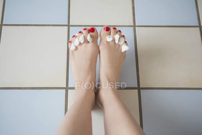 Regardant vers le bas de la vue de pieds féminins avec tissus entre les ongles d'orteil peintes sur sol carrelé — Photo de stock