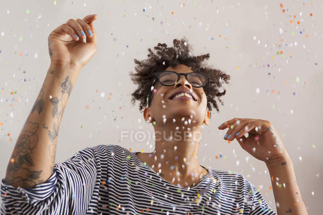 Happy young woman enjoying confetti falling on gray background — Stock Photo